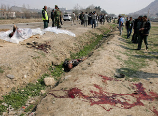 Blood stains and bodies are seen at suicide car bomb attack site in Kabul