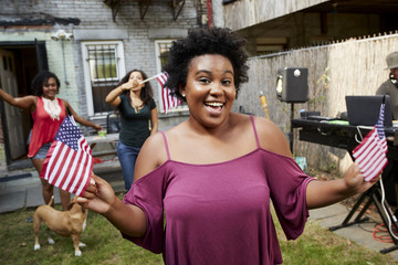 Women celebrating with American flags in backyard