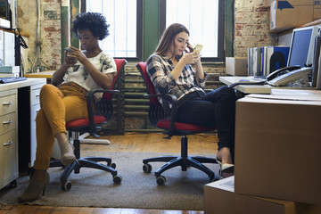 Distracted businesswomen using cell phones in office