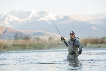 Caucasian man fly fishing in river