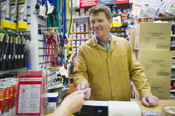 Customer paying Caucasian worker with credit card in hardware store
