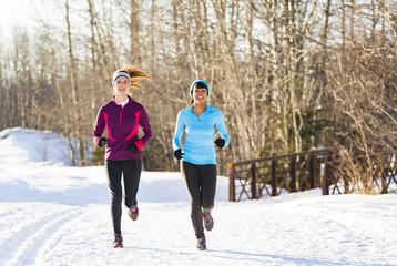 Women running on snow in winter