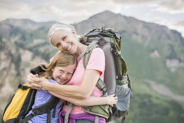 Caucasian grandmother hugging granddaughter on mountain