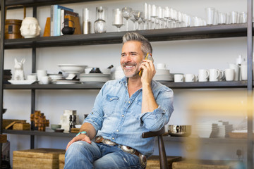 Caucasian man sitting in store talking on cell phone