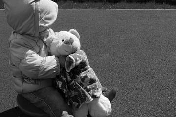 A small child in a jacket and hat sits sideways and holds a bear cub. Sad mood. Bear is the best friend. Gray rubber backdrop background. Place for inscription
