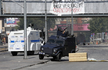 A riot police officer keeps a look out from the turret of an armoured police vehicle during clashes with protesters in Ankara