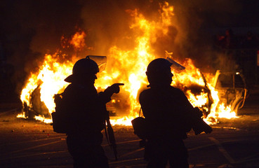 Police stand guard as police cars burn in the background after Game 7 of the NHL Stanley Cup hockey playoff between the Canucks and the Bruins in Vancouver