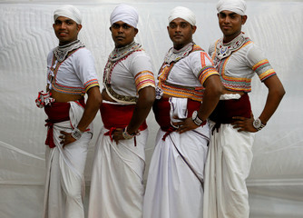 Traditional dancers pose for photographs before the performances at a Gara demon ceremony in Colombo