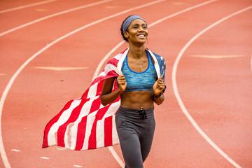 Smiling Black athlete holding American flag on track