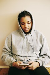 Mixed Race woman sitting on floor listening to cell phone
