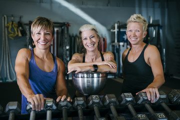 Smiling Caucasian women leaning on rack in gymnasium