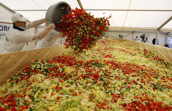 Volunteers add vegetables to create the world's biggest vegetable salad during a Guinness World Record attempt in Pantelimon