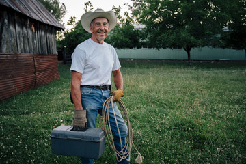 Caucasian farmer carrying rope and toolbox