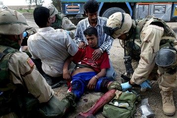 An injured Iraqi boy receives medical attention by US soldiers after stepping on an explosive device..