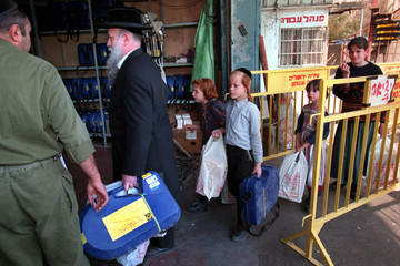 An ultra-orthodox Jewish family carry bags of old gas masks as they arrive at a mask distribution ce..