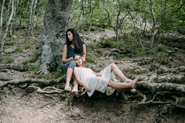 Women relaxing on tree roots in forest
