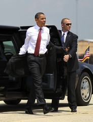 U.S. President Obama puts on his jacket as he walks towards Air Force One at Andrews Air Force Base