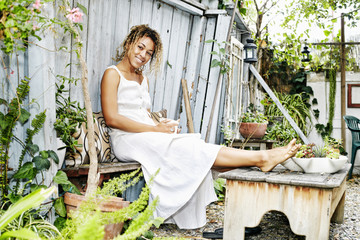 Smiling Mixed Race woman drinking coffee in garden