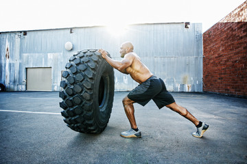 Black man working out with heavy tire outdoors