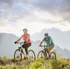 Caucasian couple riding mountain bikes