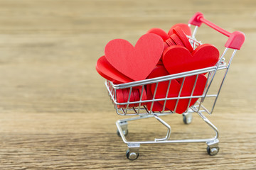 red heart shape in mini shopping cart on wooden rugged, concept of valentine day