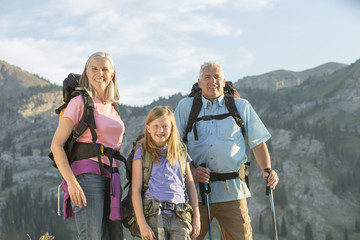 Caucasian grandparents and granddaughter hiking on mountain