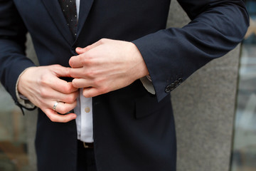 Closeup of a businessman buttoning a button in a black suit against the background of the business center with copy space
