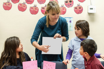 Teacher showing paperwork to students in art class