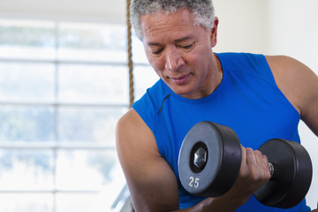 Mixed Race man curling dumbbell