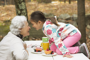 Grandmother and granddaughter playing at breakfast table outdoors
