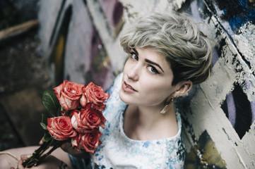 Caucasian woman at graffiti wall holding flowers