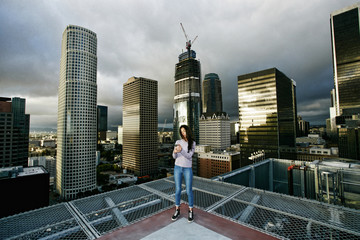 Hispanic woman texting on cell phone on urban rooftop