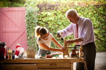 Grandfather and granddaughter building birdhouse in garage