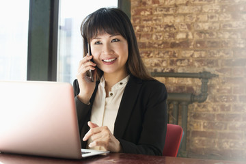 Asian businesswoman using cell phone and laptop