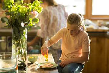 Caucasian girl squeezing honey from bottle onto pancake