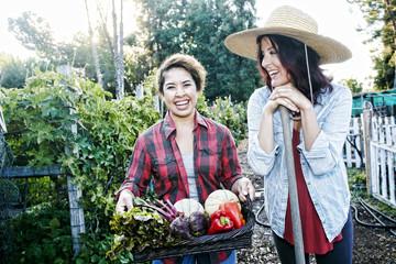 Portrait of women with basket of vegetables in garden