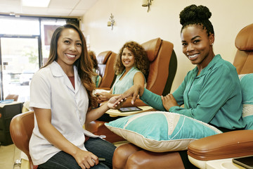 Portrait of business owner and customers in nail salon