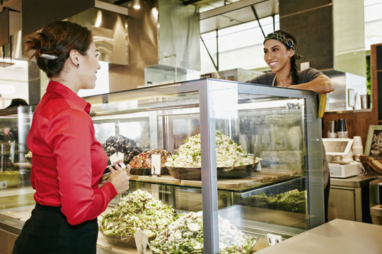 Worker assisting businesswoman in food court