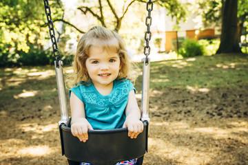 Caucasian preschool girl sitting in swing