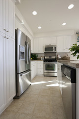 Kitchen having white cabinets and stainless steel refrigerator at home