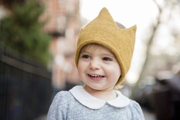 Smiling Caucasian baby girl wearing crown hat