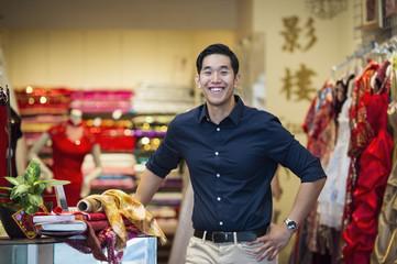 Smiling Chinese man posing in store