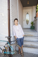 Smiling woman leaning on wall near bicycle