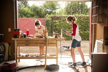 Sisters building birdhouse in garage