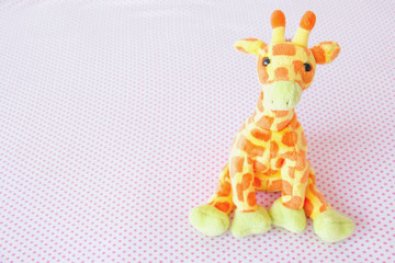 Giraffe cute are seating on pink fabric.