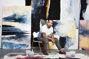 Pacific Islander artist sitting with paintings