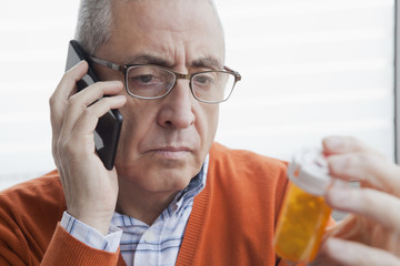 Serious Hispanic man talking on cell phone holding prescription bottle