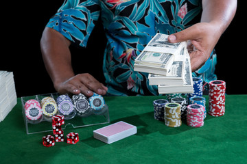 Banknote in hand and chips with casino devices on green table
