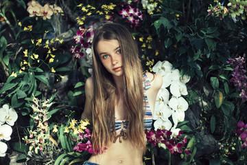 Caucasian woman wearing bikini sitting in flowers