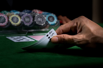 Game of blackjack at a casino with chips on a green blackjack table